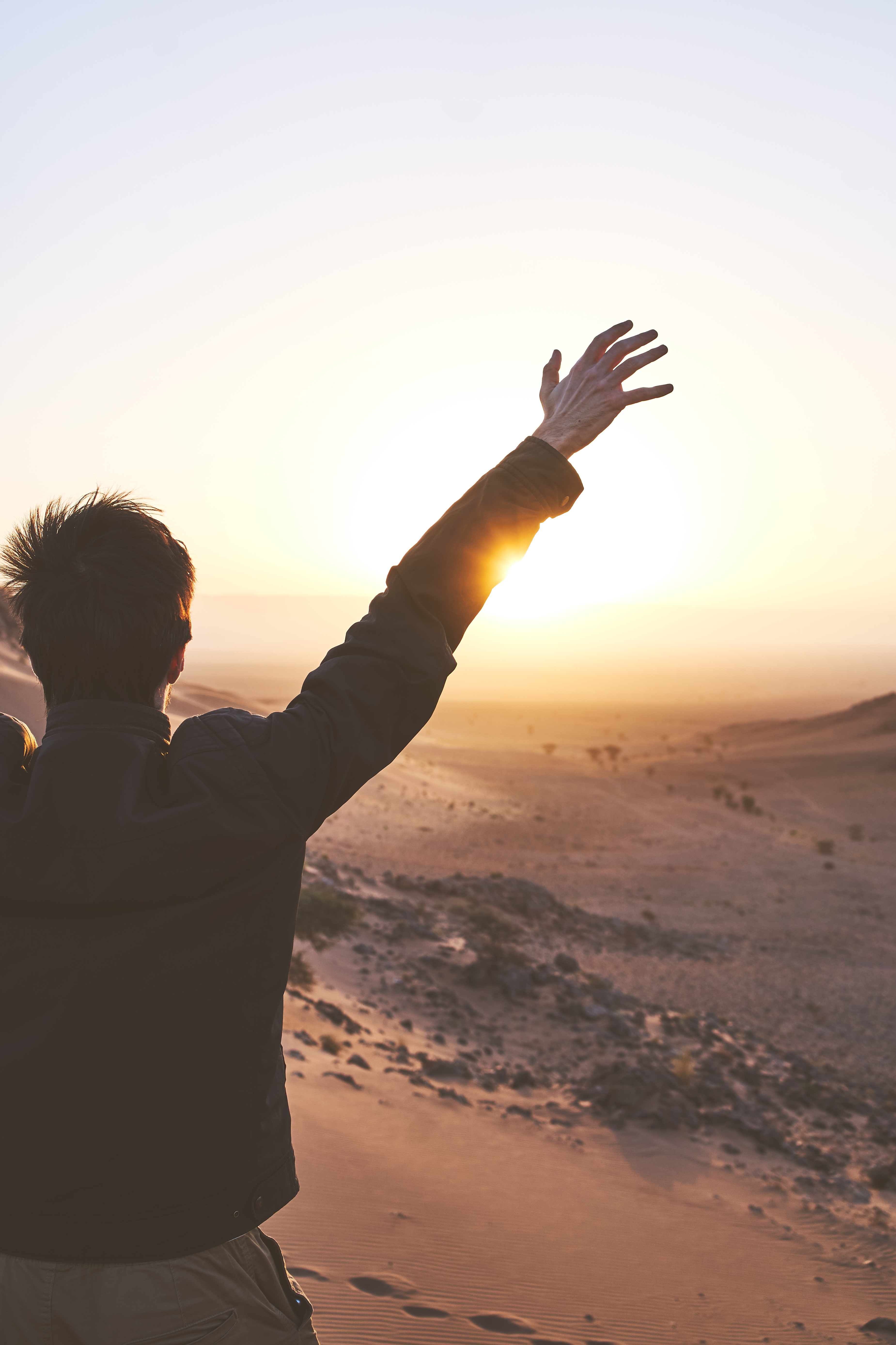 A man holding arms up in a desert on a sunrise
