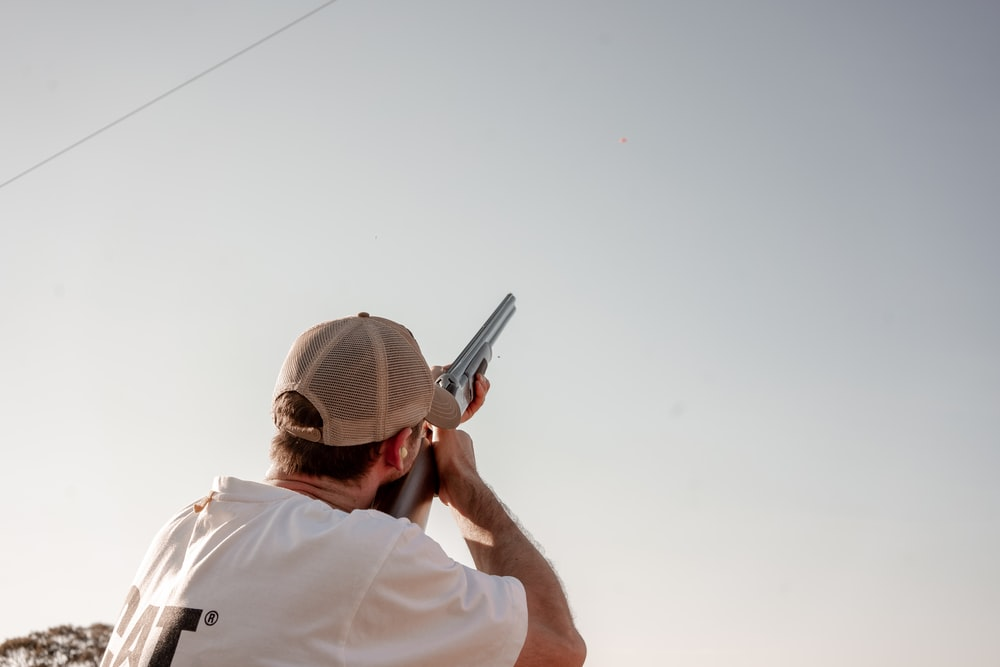 man pointing gun on sky