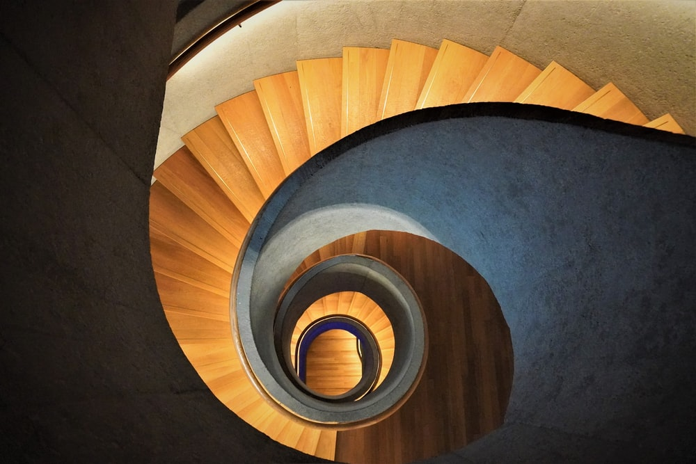 high-angle photo of brown wooden spiral staircase