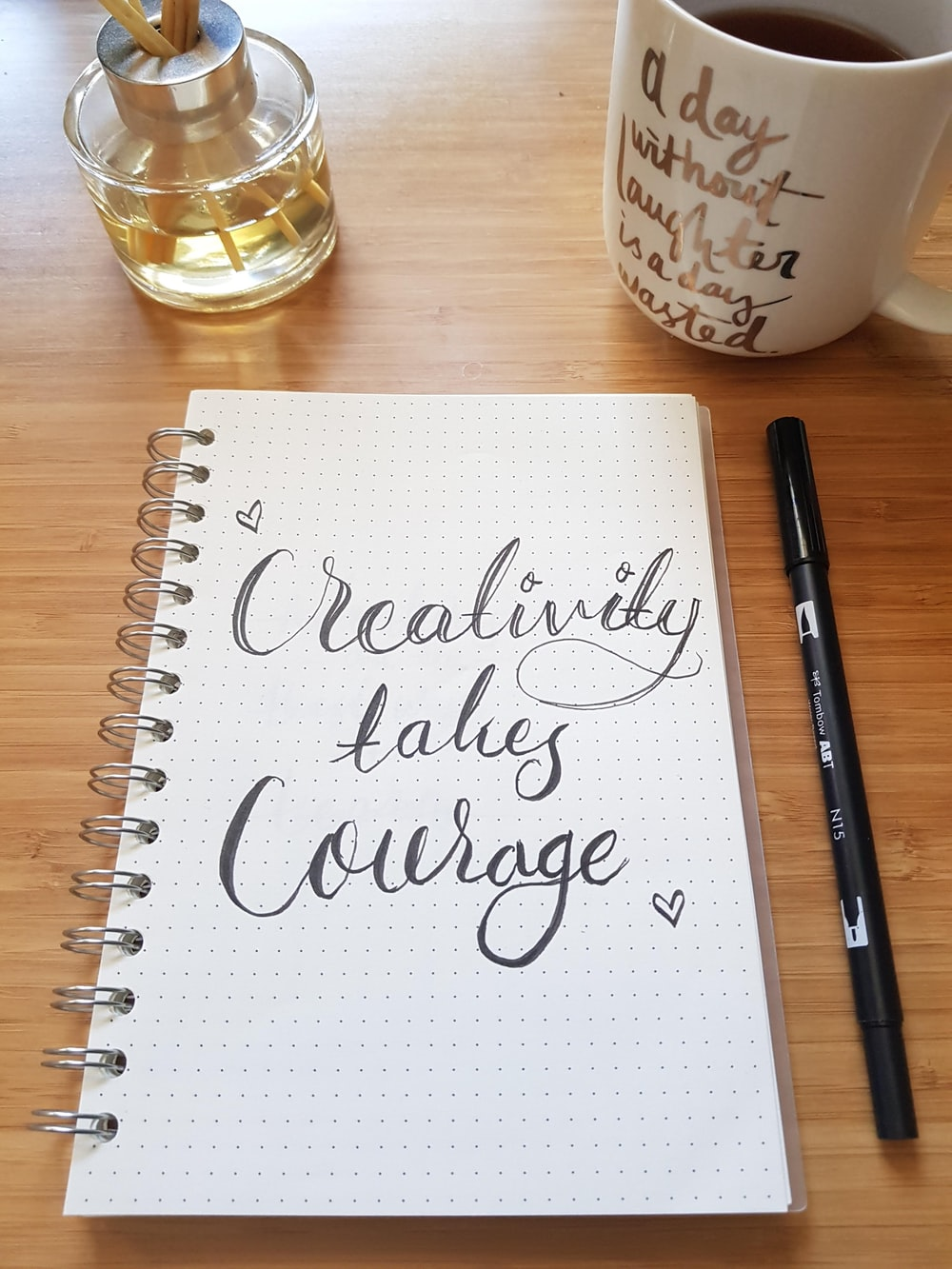 black pen beside white spiral notebook