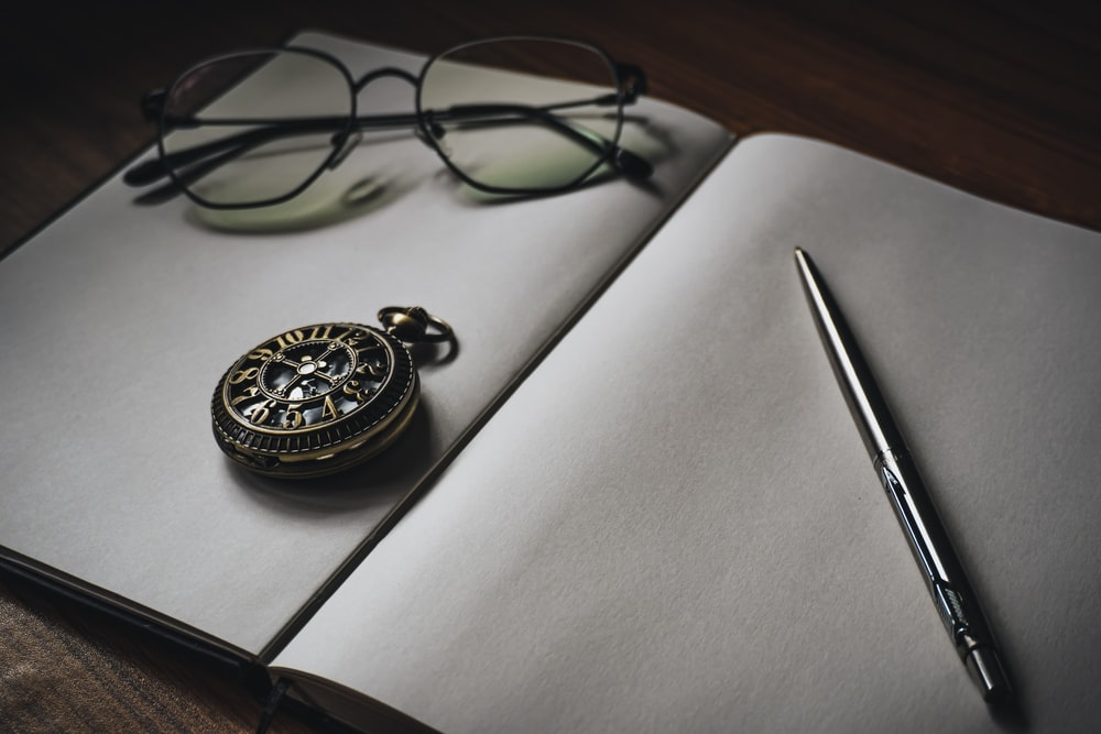 pocket watch, eyeglasses, and pen on blank opened book