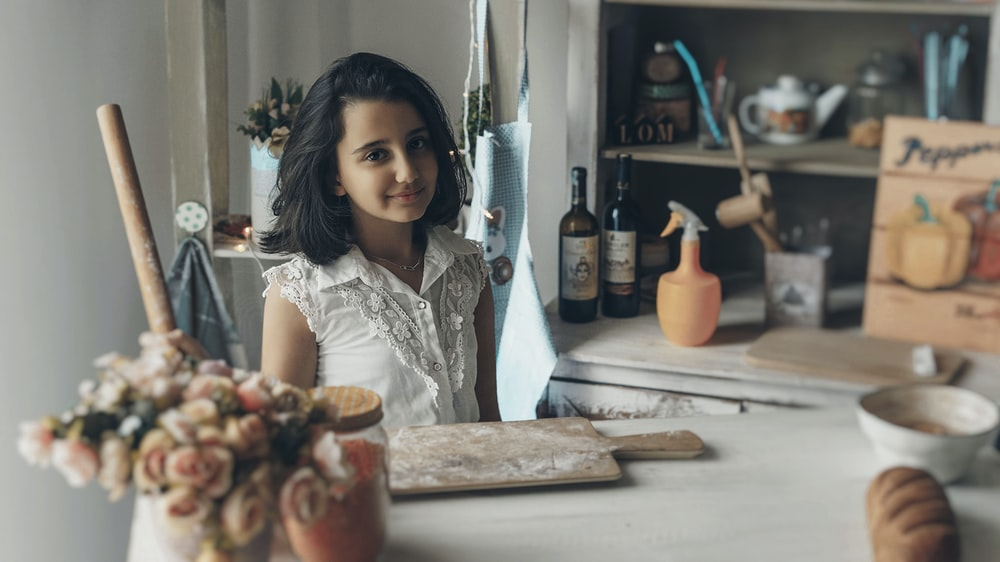 girl smiling and looking at the camera beside chopping board with flour