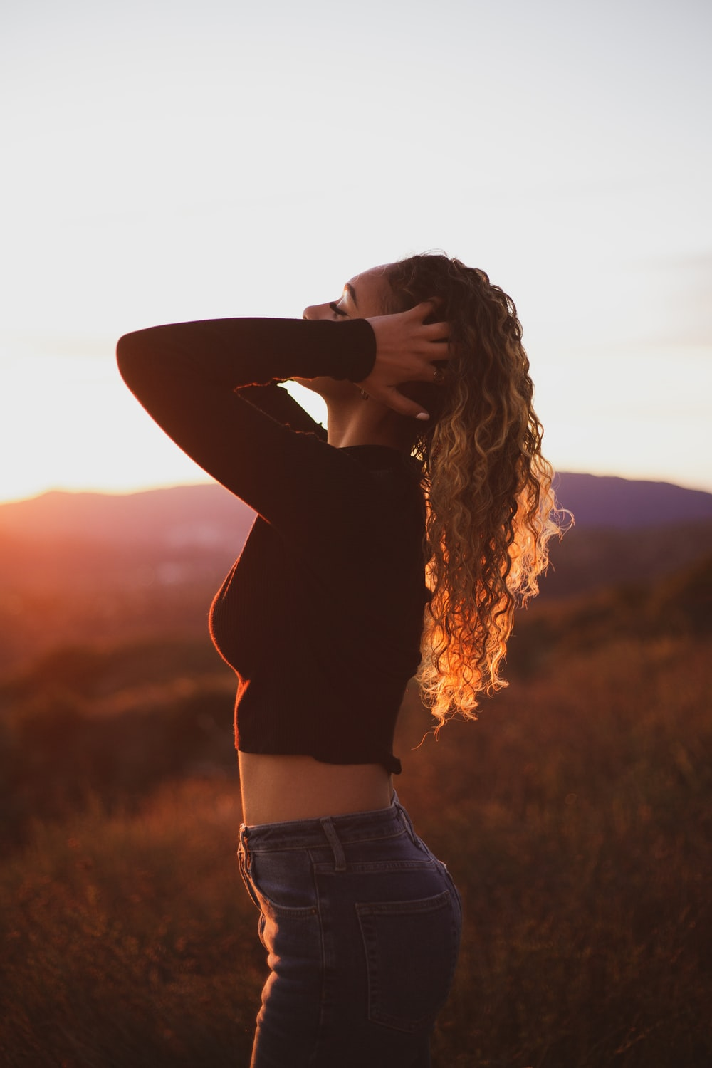 woman standing with both hands touching her hair during day