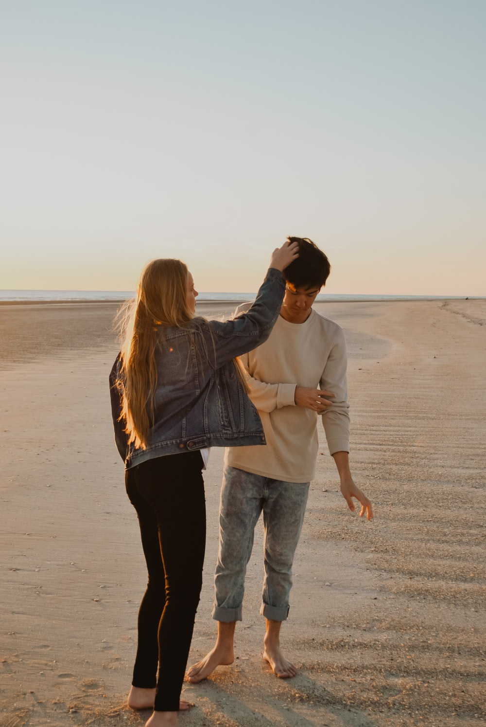 couple standing on sand during daytime