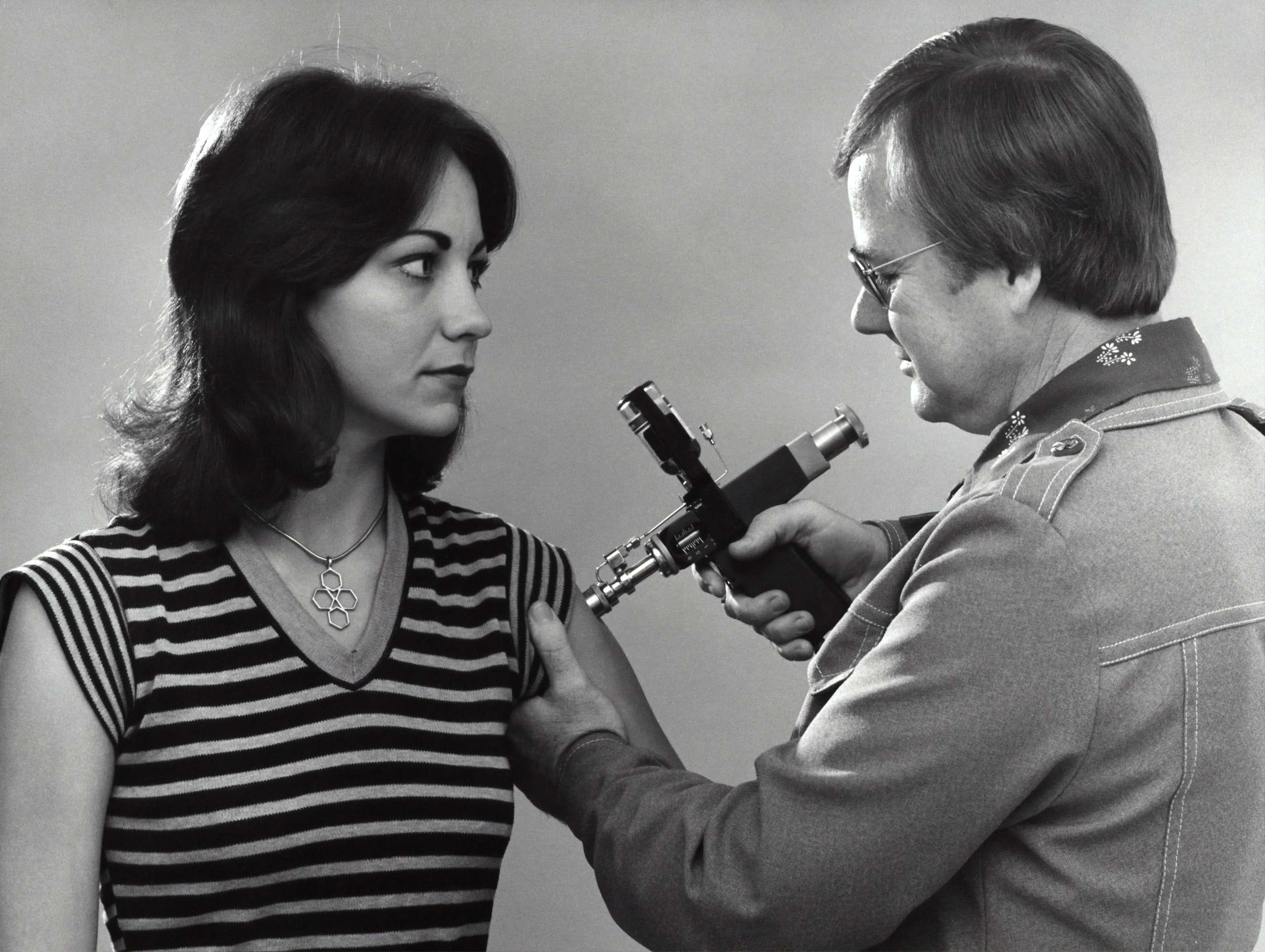 """Created in 1976, this historic photograph showed an adult female receiving a vaccination that was administered by a public health clinician, by way of a jet injector, also known as a """"Ped-O-Jet®"""", during the nationwide Swine Flu vaccination campaign, which began October 1, 1976."""