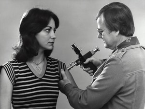 "Created in 1976, this historic photograph showed an adult female receiving a vaccination that was administered by a public health clinician, by way of a jet injector, also known as a ""Ped-O-Jet®"", during the nationwide Swine Flu vaccination campaign, which began October 1, 1976."
