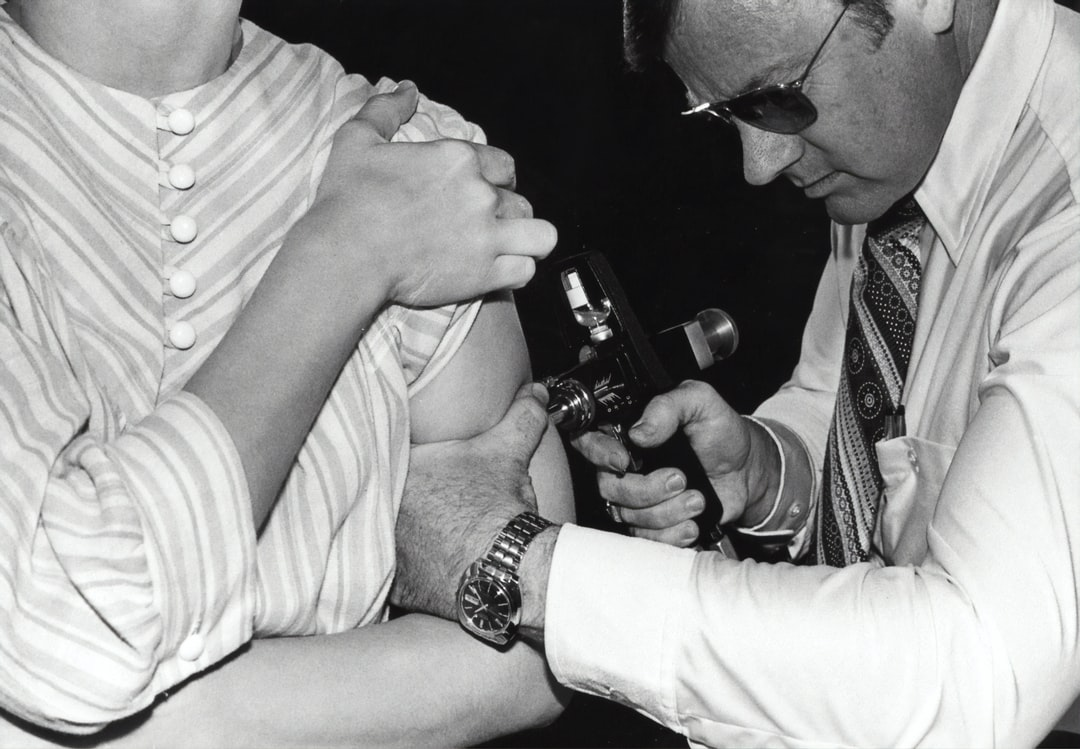 """Created in 1976, this historic photograph showed an adult receiving a vaccination with a jet injector, also known as a """"Ped-O-Jet®"""", during the Swine Flu nationwide vaccination campaign, which began October 1, 1976."""