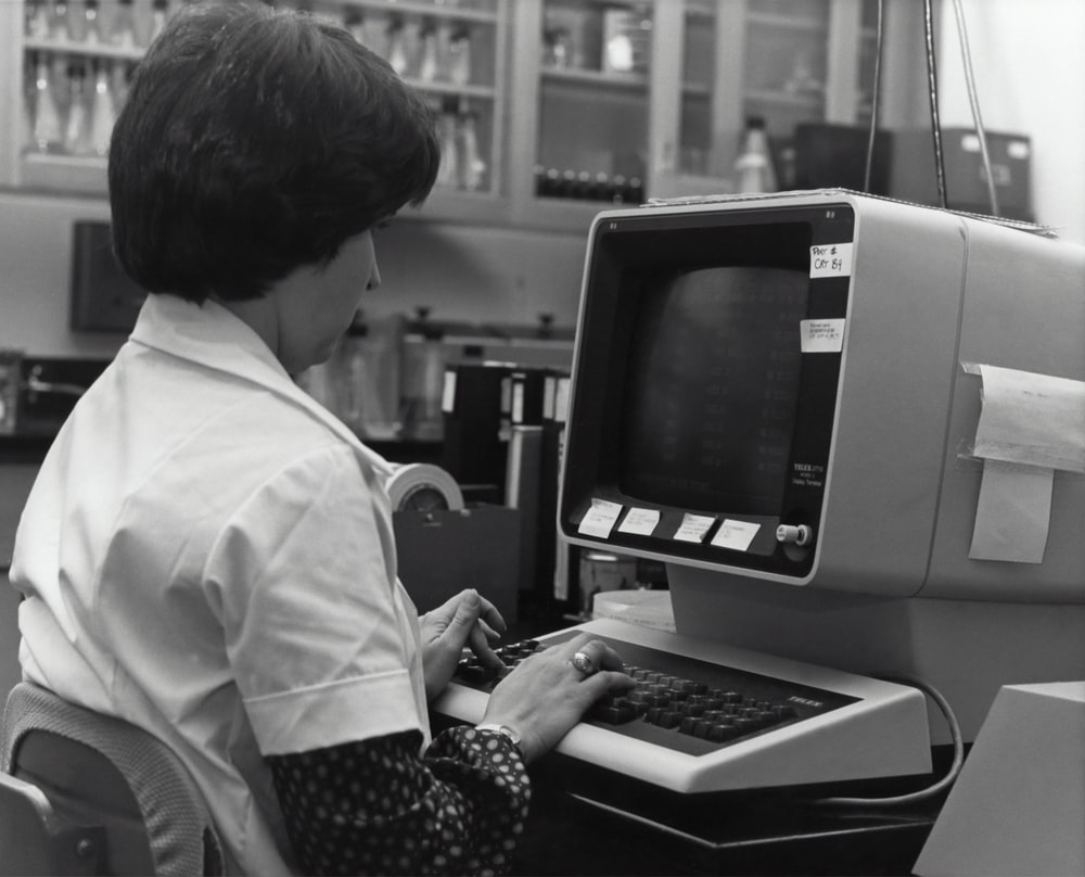 grayscale photography of unknown person using computer