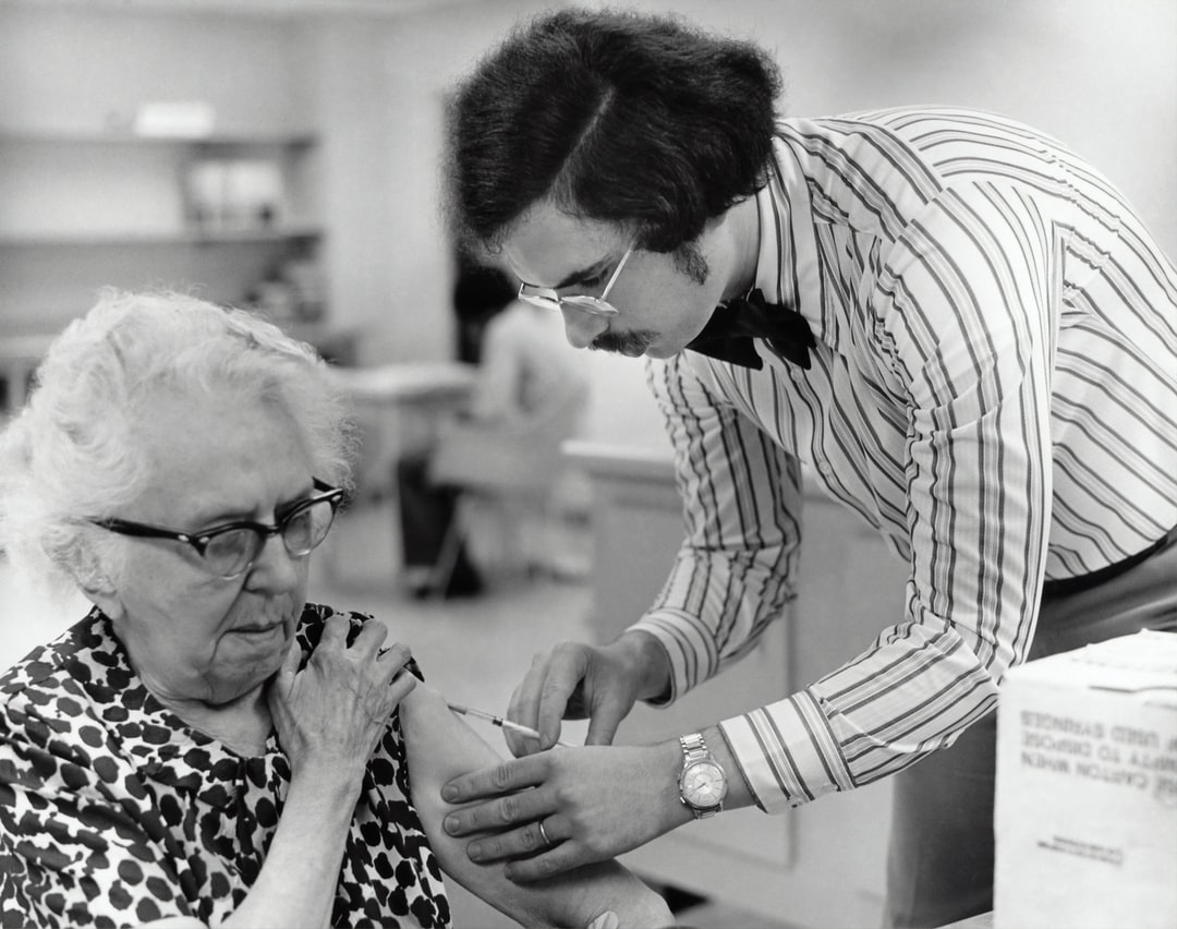 Created in 1976, this historic photograph depicted an elderly female as she was receiving a vaccination by a public health clinician during the nationwide Swine Flu vaccination campaign, which began October 1, 1976.