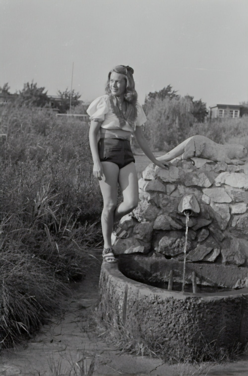 grayscale photography of woman standing near water well