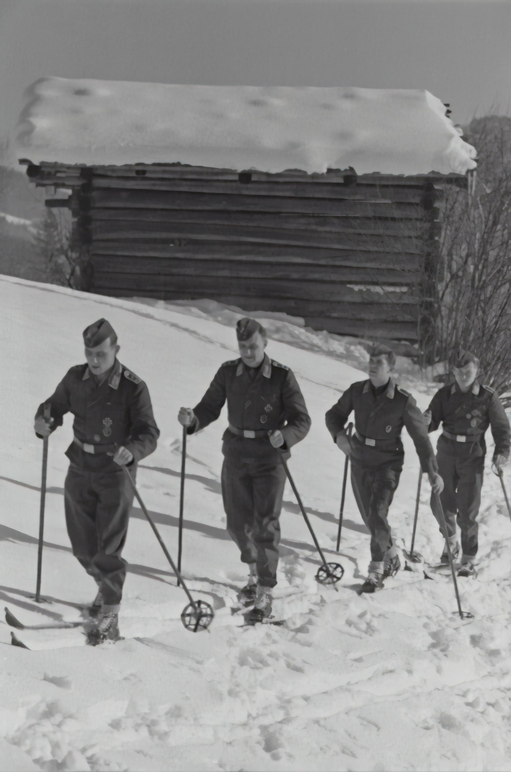 grayscale photography of four men walking on snow