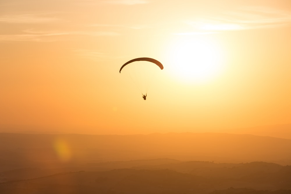 person parachuting during golden hour