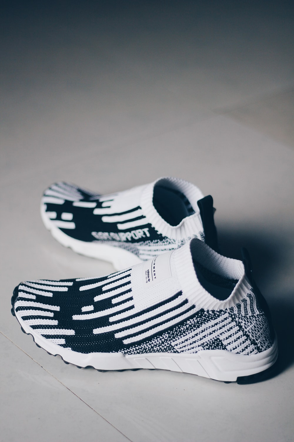shallow focus photo of pair of white-and-black running shoes