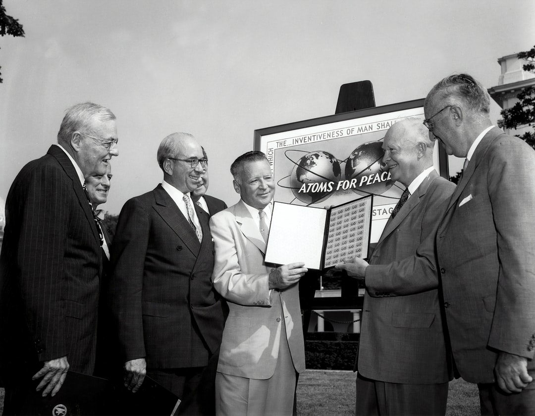 President Eisenhower receives an album of Atoms-for-Peace stamps.