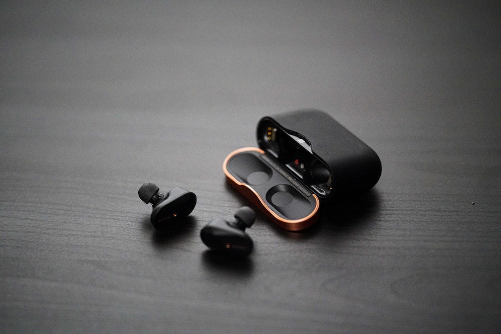 black wireless earphones on surfae