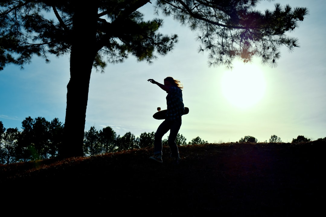 boy finds new spot to skateboard; silhouette sunset