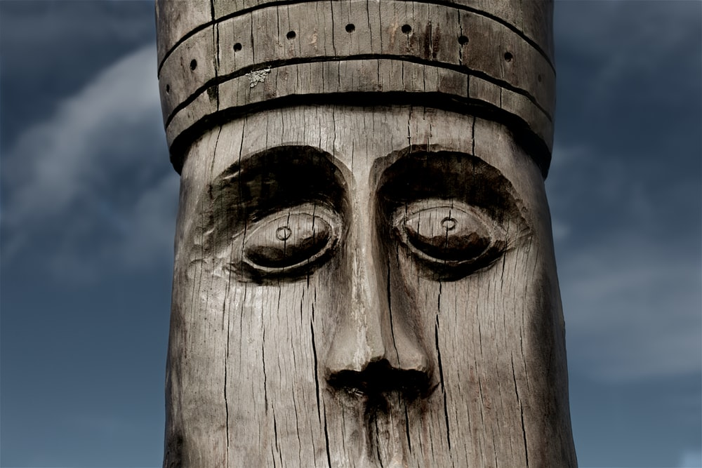 close-up photography of brown wooden statue during daytime