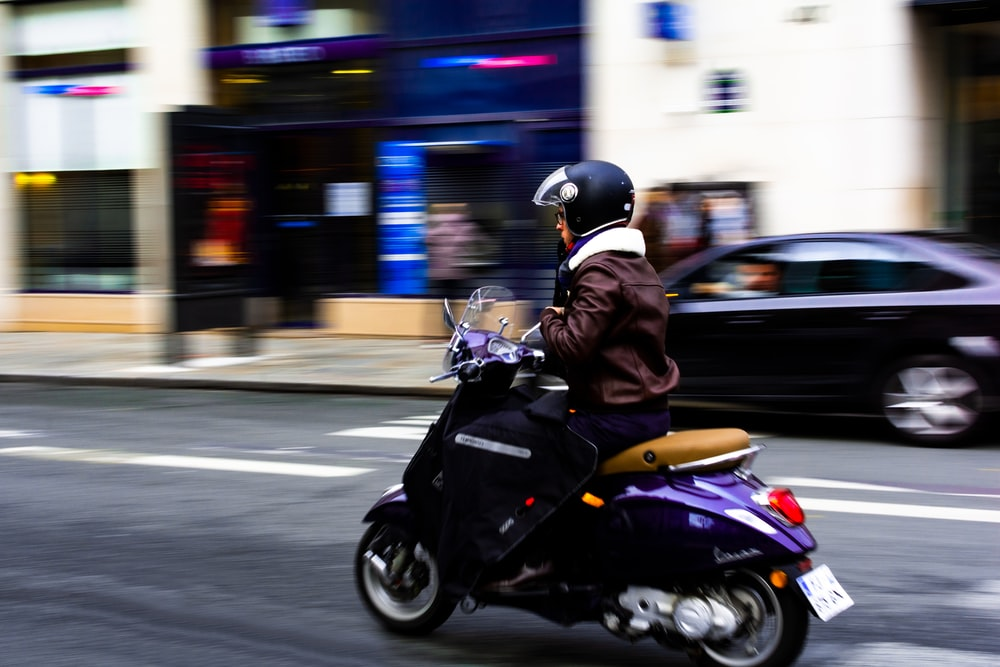 person driving the purple motor scooter