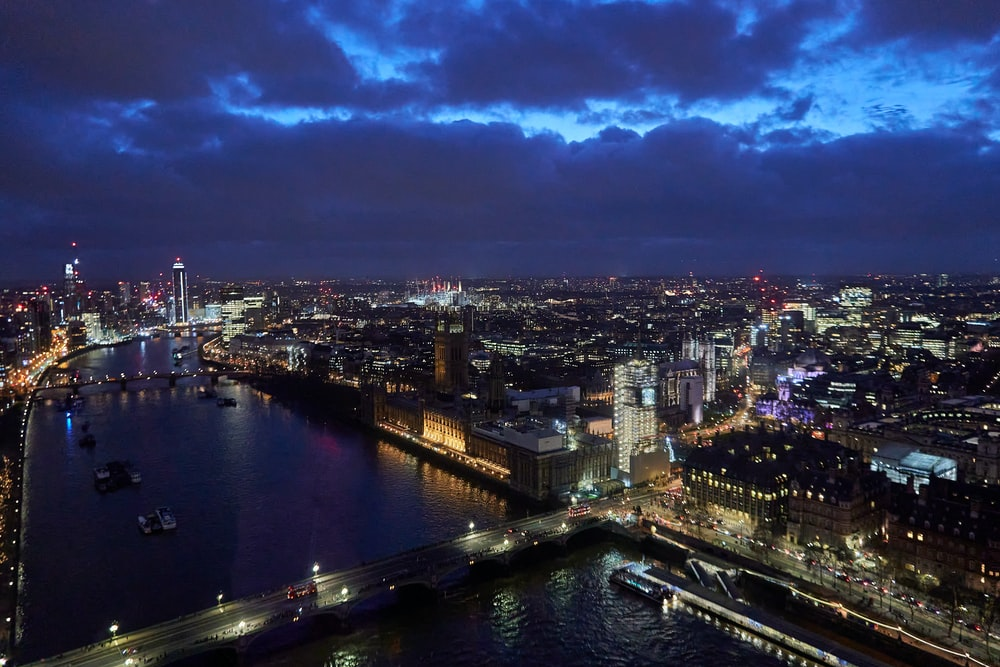 aerial photography of city with high-rise buildings near body of water during night time