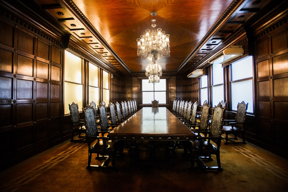 rectangular brown wooden long table inside building and lighted crystal chandelier