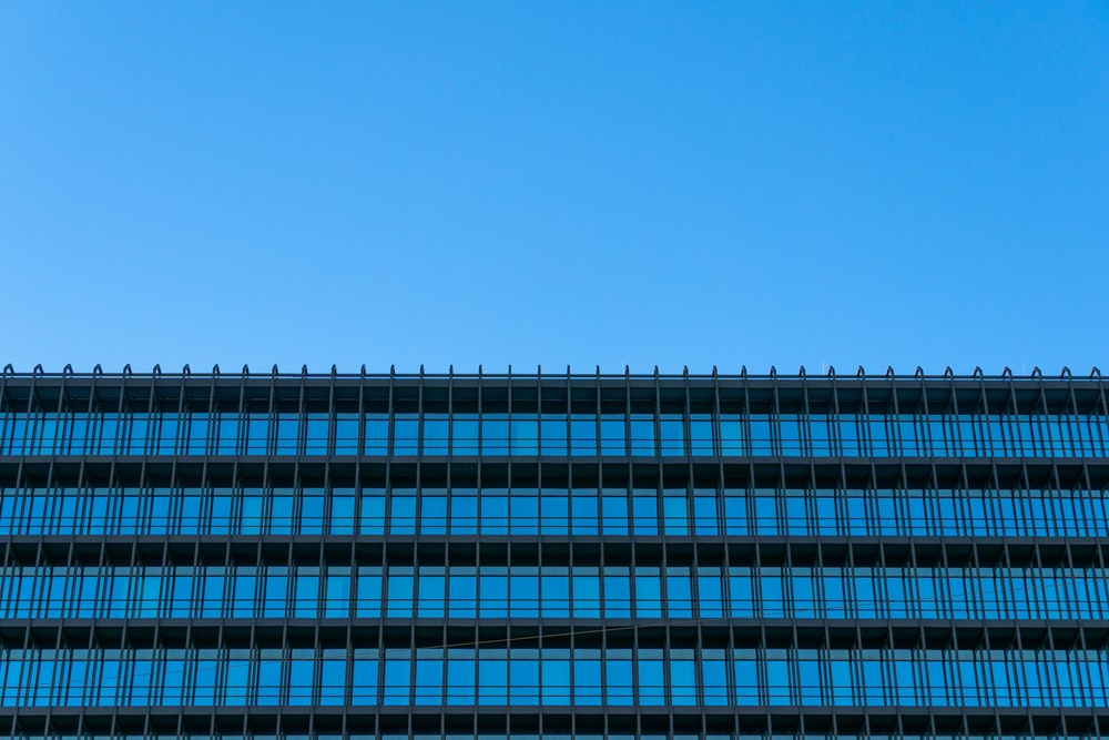 architectural photography of blue and gray glass walled building