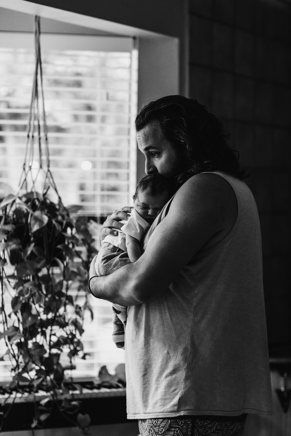 grayscale photography of man wearing tank top carrying newborn baby while standing near window