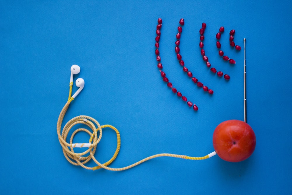 white earbuds connected to orange tomato with antenna