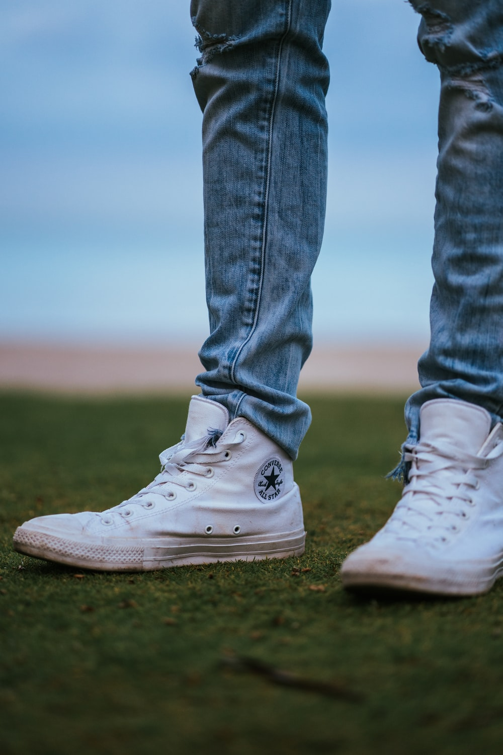 man wearing white Converse high-tops shoes