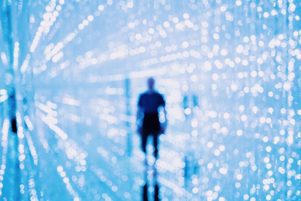 man stands behind bokeh lights