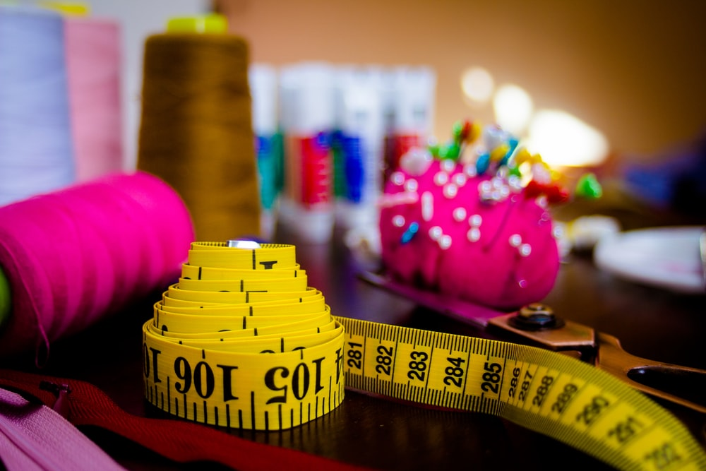 measuring tape beside thread spools and pins in pin cushion