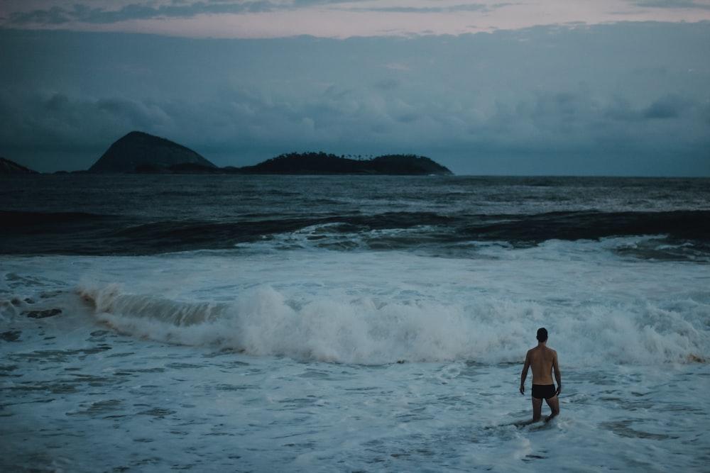 man standing beside seashore during daytime