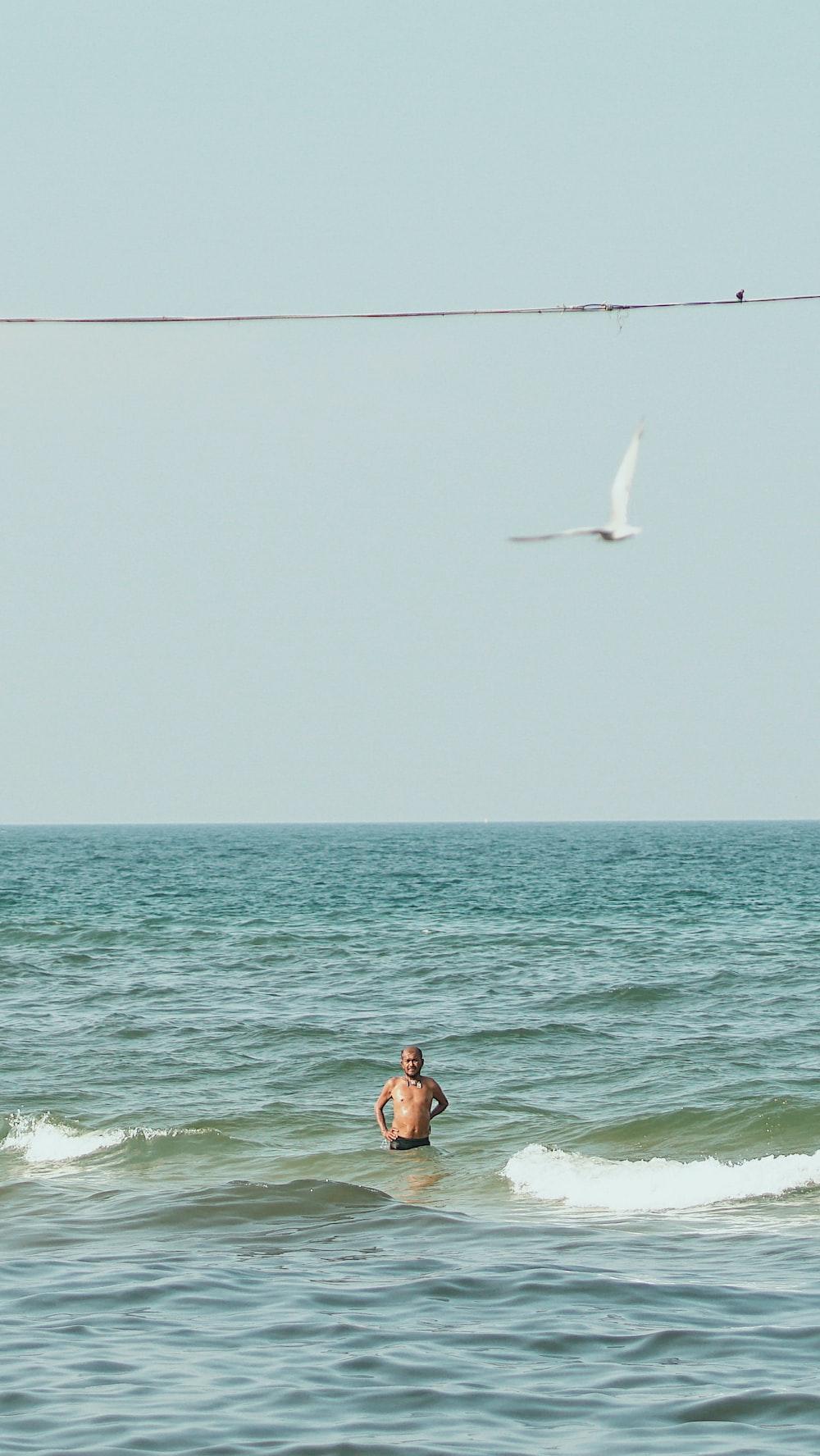 person taking bath on sea
