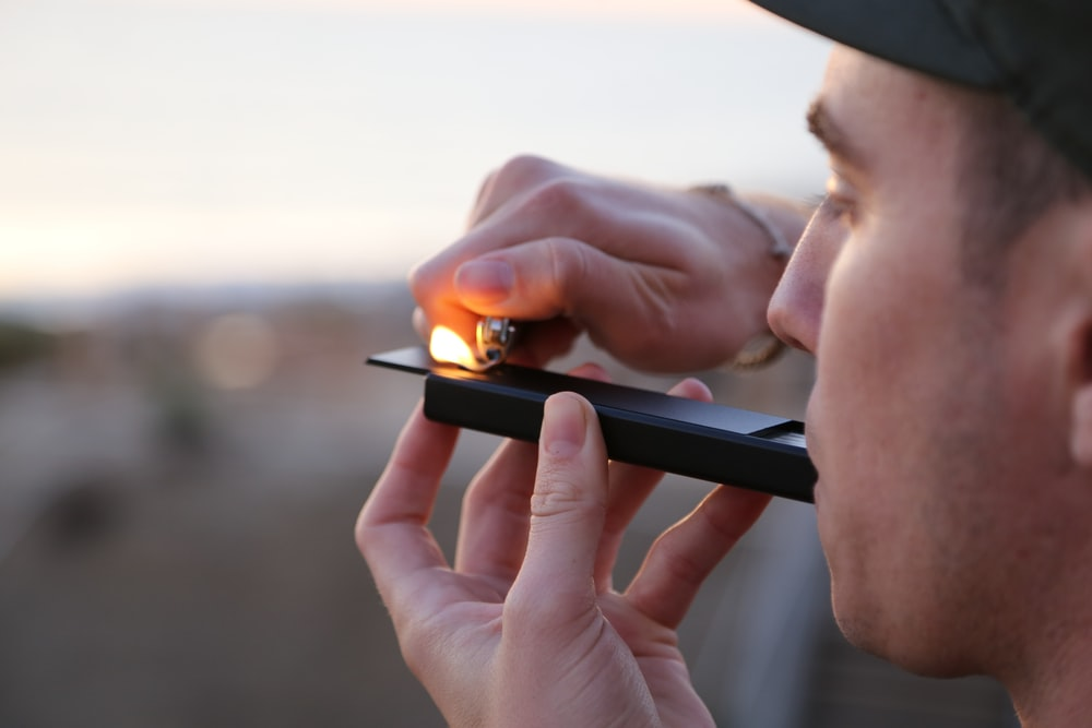 man doing smoke during daytime