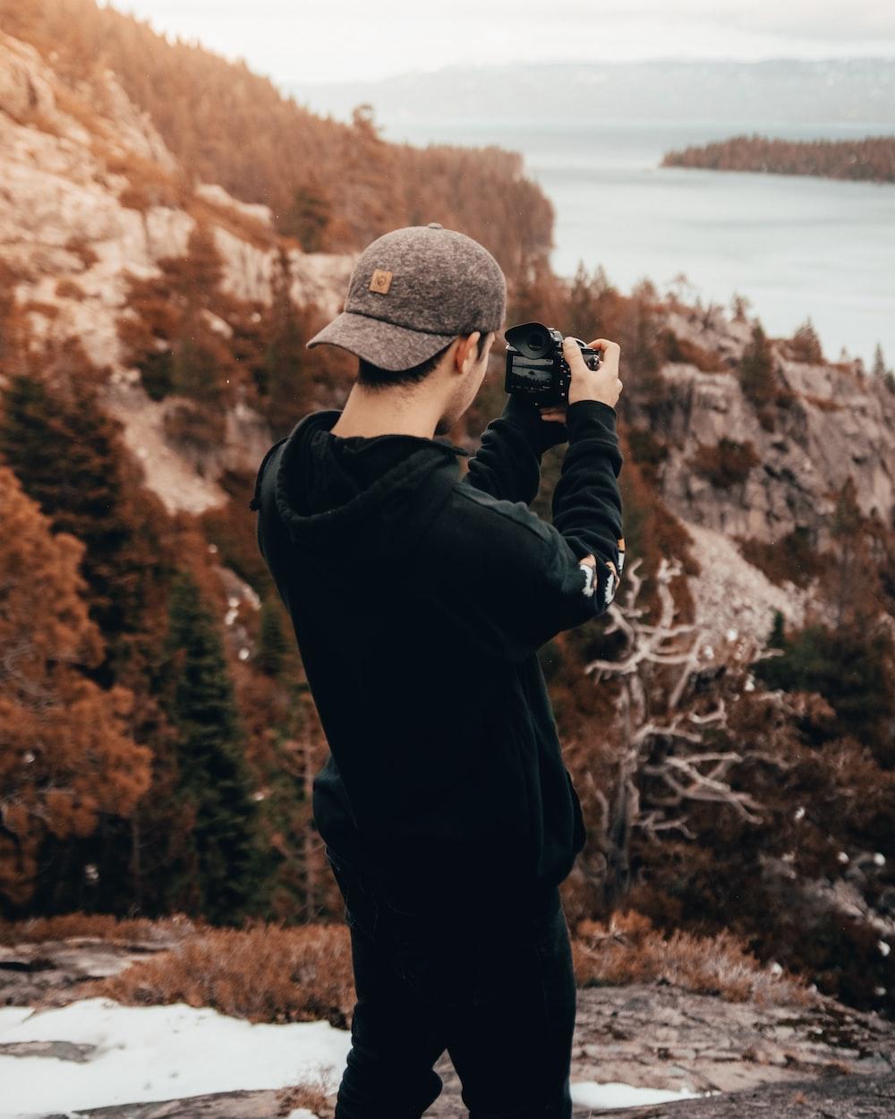 man taking photo in mountain during daytime