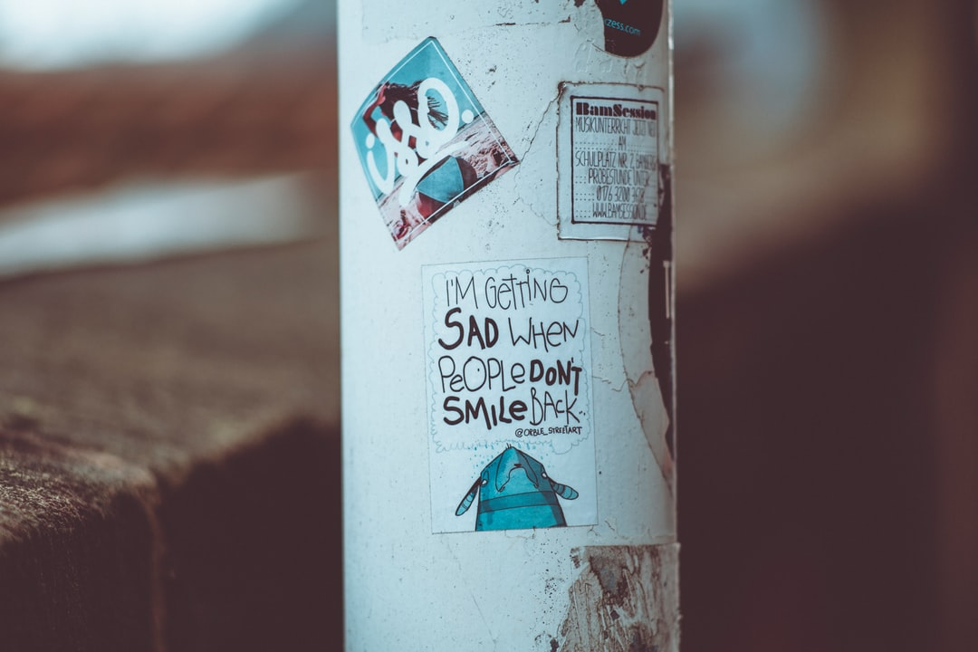 I'M GETTING SAD WHEN PEOPLE DON'T SMILE BACK. Urban street art sticker. Made with Canon 5d Mark III and analog vintage lens, Leica Elmarit-R 2.8 135mm (Year: 1987)