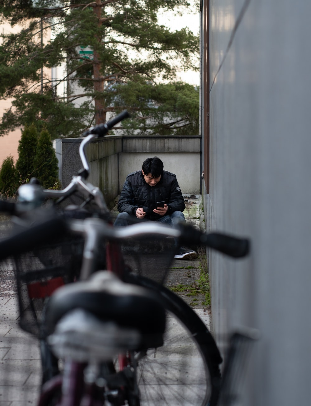 selective focus photography of man sitting near parked bike beside wall