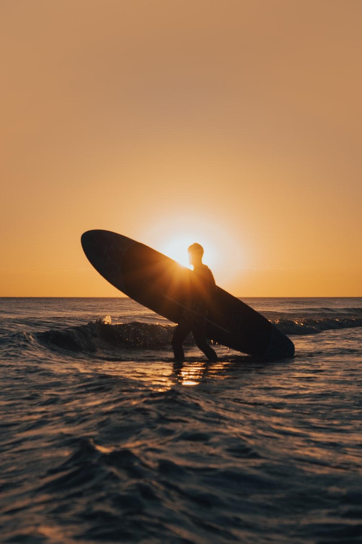 man holding surfboard on the seashore