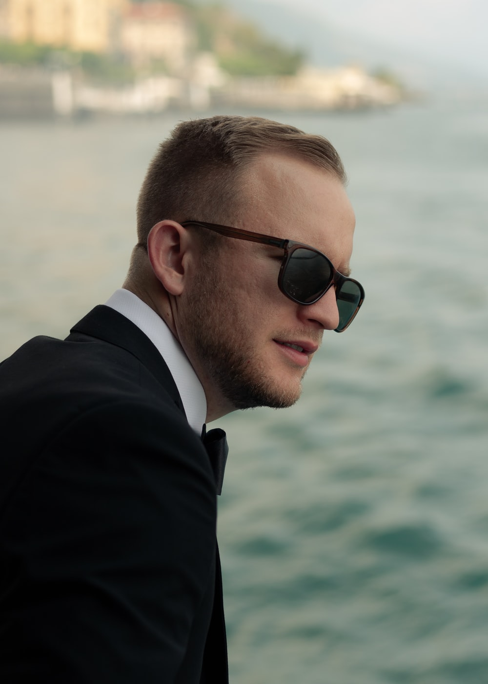 man wearing black tuxedo and black wayfarer sunglasses