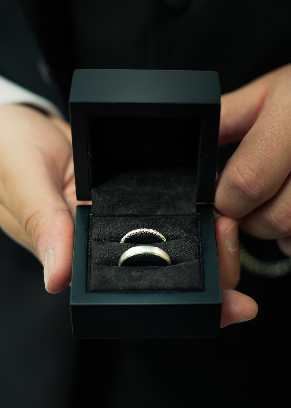 person holding two silver-colored rings with box