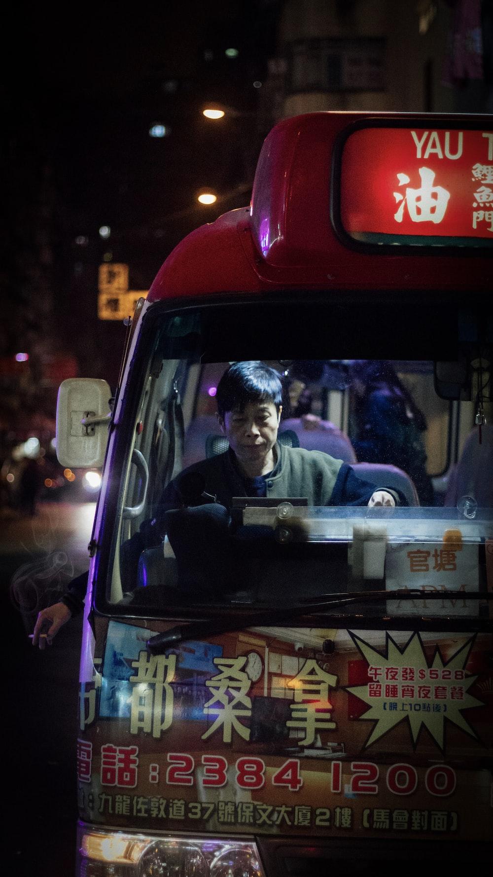 man sitting inside bus at night
