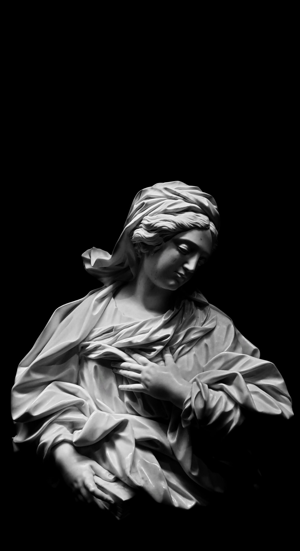 grayscale photography of woman with left hand on chest statue