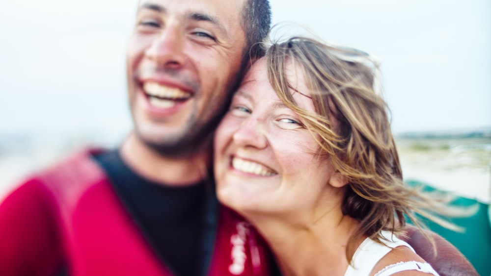 smiling woman and man hugging during daytime