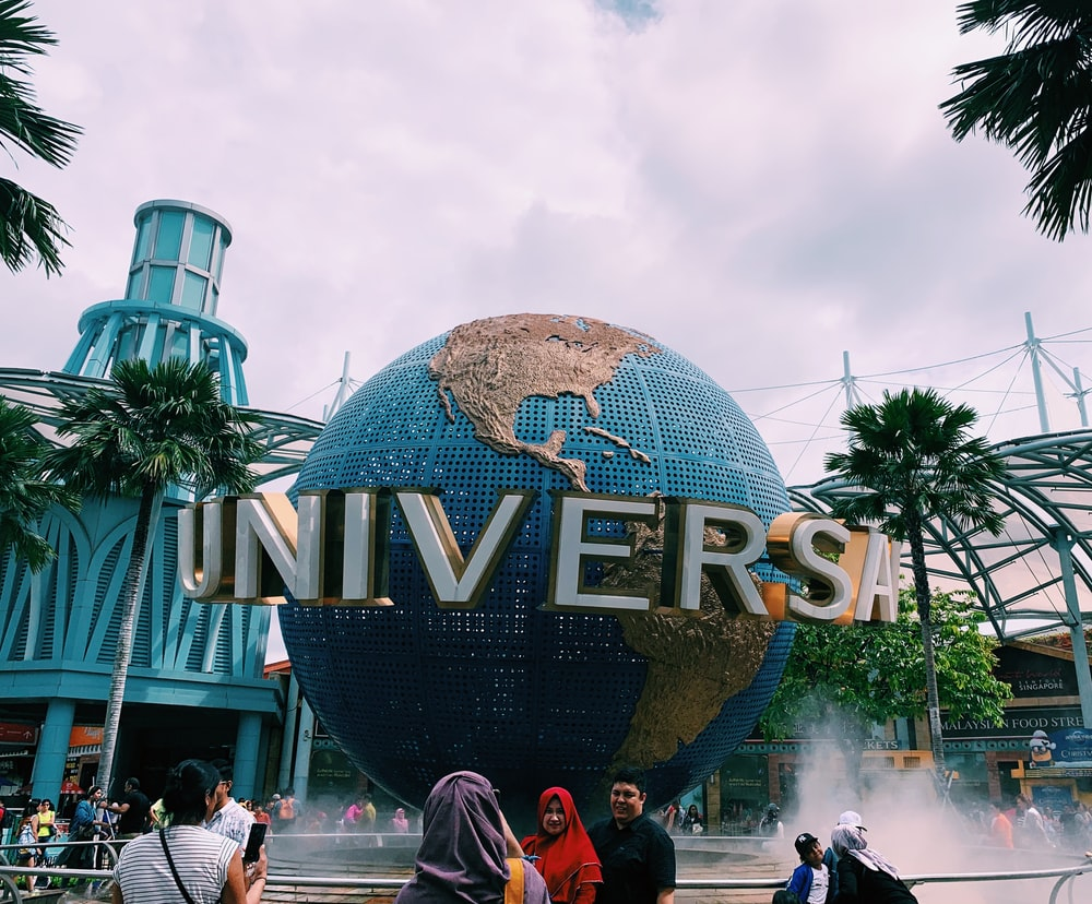 people taking photos in front of Universal globe
