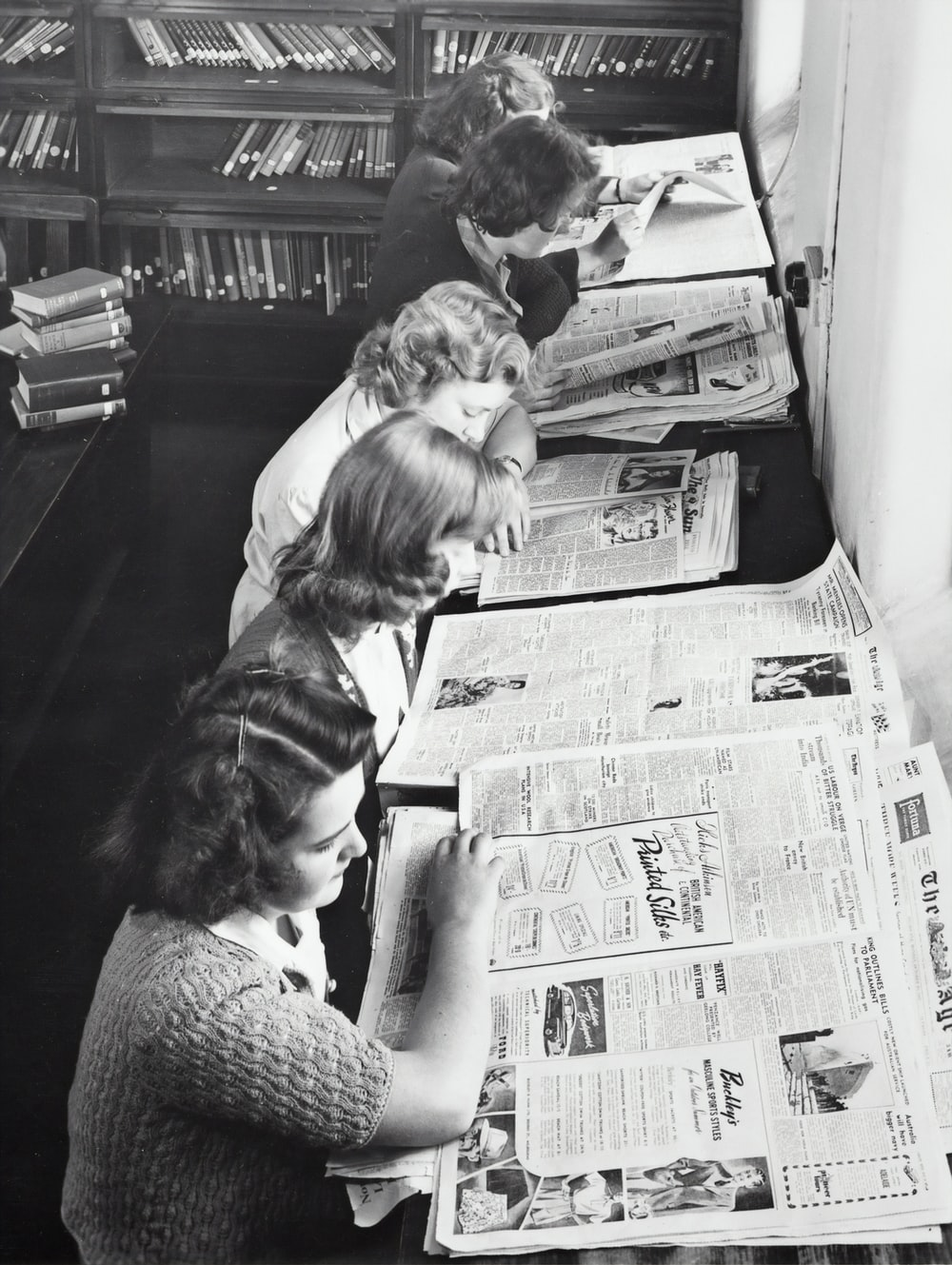 grayscale photo of women reading newspaper