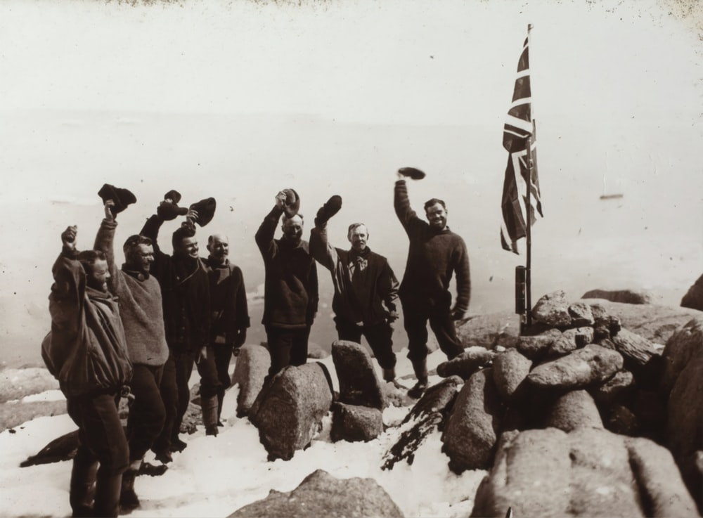 grayscale photo of men standing beside flag