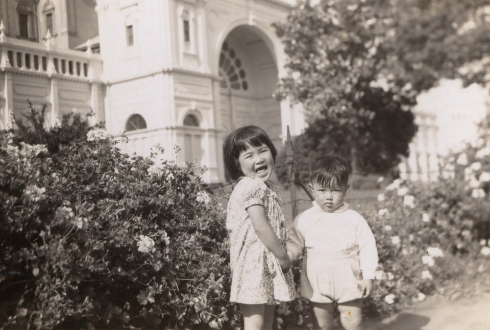 grayscale photography of girl and boy standing near flowers