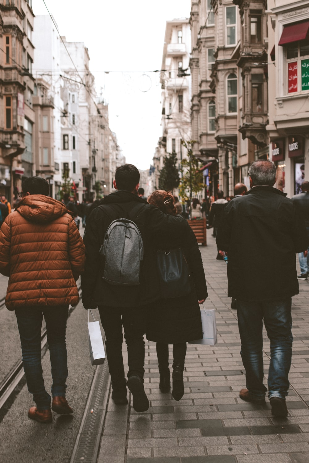 four persons walking on street during daytime