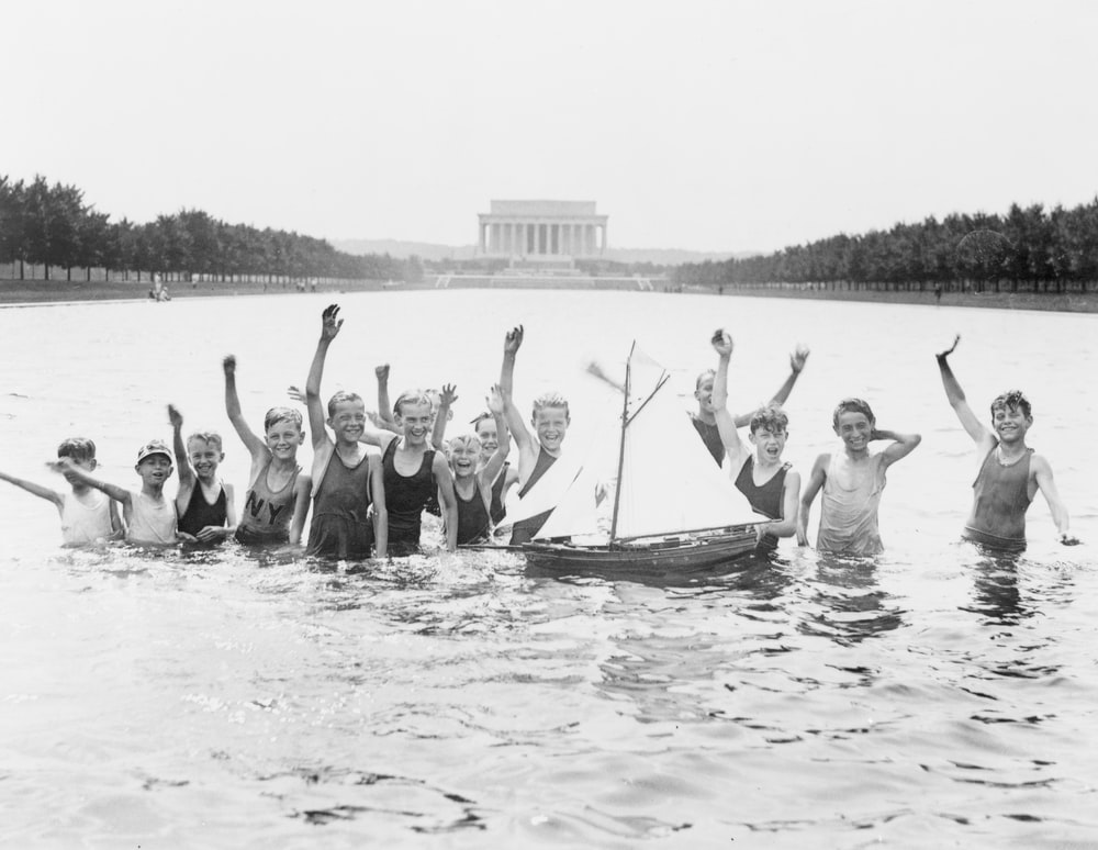 Group of boys waving as they play in the reflecting pool in front of the Lincoln Memorial