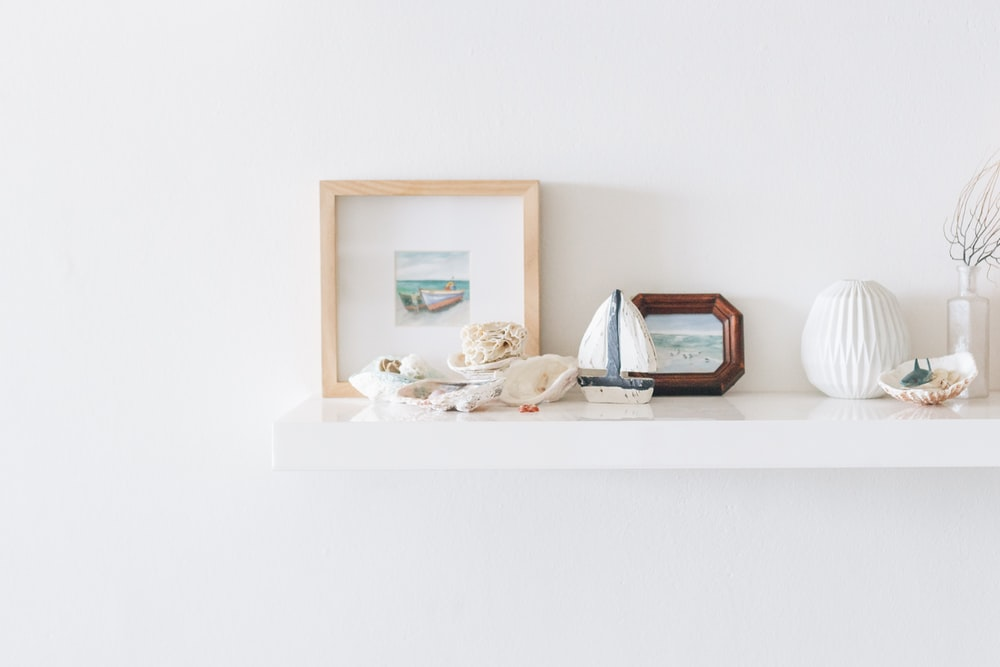 brown photo frame beside wall