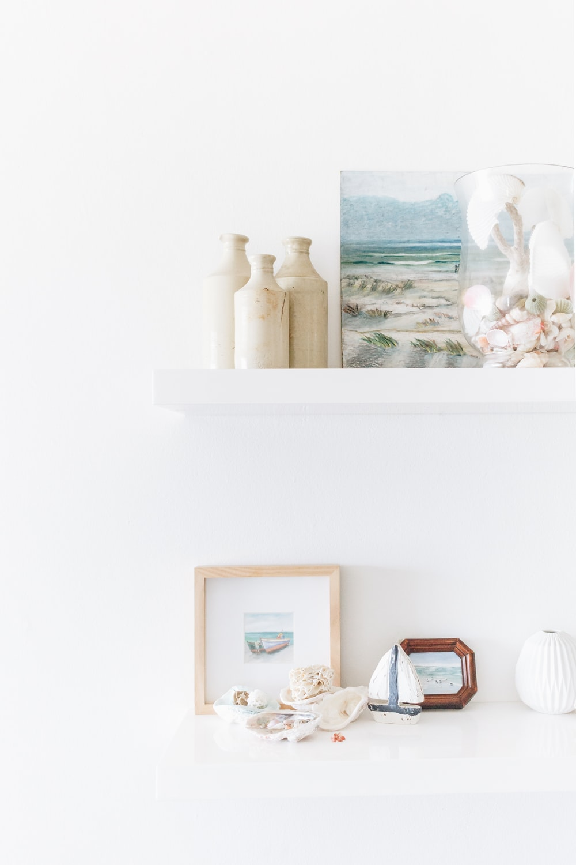 three white plastic bottles beside painting